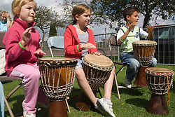 Group of children taking part in a drumming workshop at a Parklife summer activities event,
