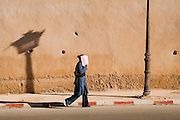A woman walks by holding up a pink sheet of paper covering her face to protect her from the hot sun in Meknes, Morocco on November 1, 2007.