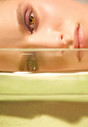 Close up of a young woman face lying behind a glass container
