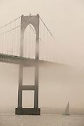 USA - Newport, RI - Twelve meter Courageous sails under the fog covered Newport bridge.