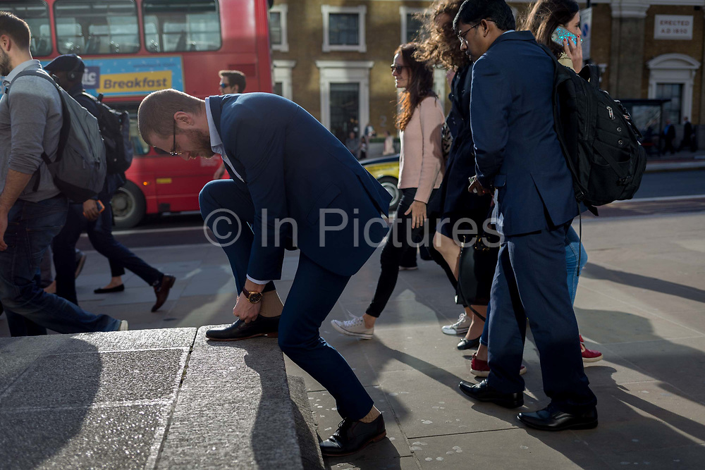 A man stops to tie a shoe lace while other commuters and pedestrians walk over London Bridge, the oldest of the capitals crossing over the river Thames between the capitals financial district, the City of London, and Southwark on the south bank, on 17th May 2018, in London, UK.