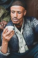 Addis Ababa, Ethiopia - July 31, 2010: A man drinks Ethiopian coffee on a sidewalk in Addis Ababa, Ethiopia.