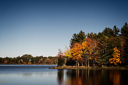 A view of a lake along Route 17 in Maine on a clear, blue sky, October day.