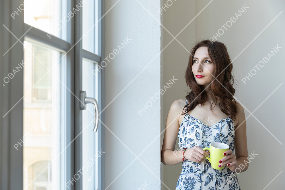 Young girl stays at the window standing with a cup in her hand thoughtfully