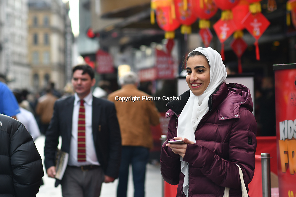A Muslim lady watching a Japanese lady dancing and busking at Leicester Square, London, UK 23 September 2018.