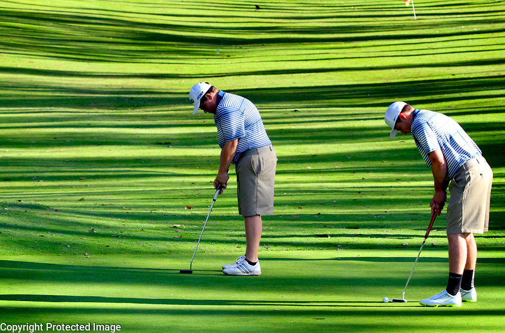 Afternoon sunlight and shade streak the second fairway at Seascape Golf Club in Aptos, California as Aptos High teammates Max Meltzer and Beau Kittleson line up their putts on the green during the Mariners' match against Scotts Valley High School.<br /> Photo by Shmuel Thaler <br /> shmuel_thaler@yahoo.com www.shmuelthaler.com