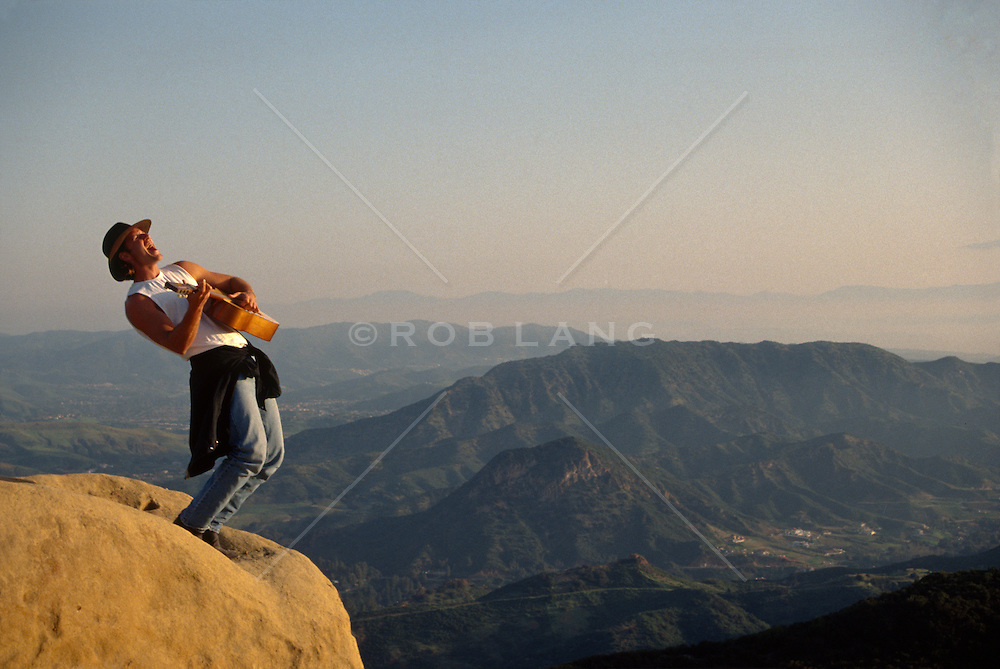 Man playing the guitar and singing while standing on a rock formation in California