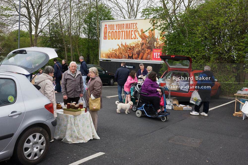 Locals sift through possessions below a Goodtimes ad during a Sunday car boot sale in a supermarket car park.