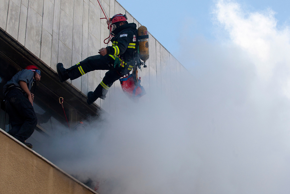 Israeli fire-fighters practice rescuing casualties from a burning building, as part of a day-long war drill in Jerusalem on November 30, 2010.