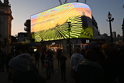 © Licensed to London News Pictures. 01/05/2021. London, UK. A new video work by British artist DAVID HOCKNEY titled Remember you cannot look at the sun or death for very long is shown on London's Piccadilly Lights. Created in the artists iPad, the work coincides with the release of his new book Spring Cannot Be Cancelled and his Royal Academy exhibition The Arrival of Spring, Normandy, 2020. Photo credit: London News Pictures