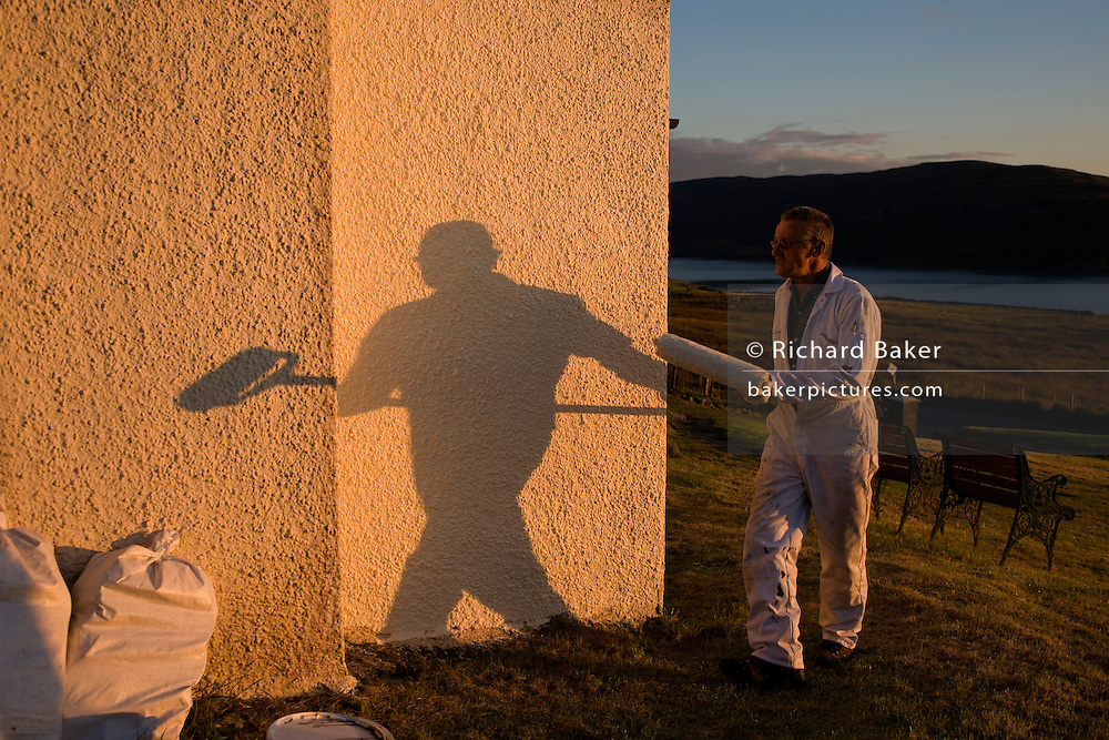 """Decorator and part-time chimney sweep Alan Squires prepares to apply another coat of emulsion paint to the exterior walls of a cottage called Burnside in the tiny hamlet of Hallin, Waternish, on the Isle of Skye, Scottish Highlands. With his shadow looming large on the newly-painted off-white pebbledash that is rendered a warm orange in the low sunlight, Alan walks with his long roller after a day's decorating in this beautiful place near Dunvegan. Alan is an Englishman who came to Skye in 1987 for the community spirit. """"everybody knows everybody' he says though admits that southerners come from the south in search of an idyllic lifestyle but harsh winters often send them back to warmer climates. Alain's fresh paint therefore needs to dry before winter weather blows in from the Atlantic. Image taken for the 'UK at Home' book project published 2008."""