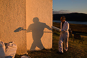 "Decorator and part-time chimney sweep Alan Squires prepares to apply another coat of emulsion paint to the exterior walls of a cottage called Burnside in the tiny hamlet of Hallin, Waternish, on the Isle of Skye, Scottish Highlands. With his shadow looming large on the newly-painted off-white pebbledash that is rendered a warm orange in the low sunlight, Alan walks with his long roller after a day's decorating in this beautiful place near Dunvegan. Alan is an Englishman who came to Skye in 1987 for the community spirit. ""everybody knows everybody' he says though admits that southerners come from the south in search of an idyllic lifestyle but harsh winters often send them back to warmer climates. Alain's fresh paint therefore needs to dry before winter weather blows in from the Atlantic. Image taken for the 'UK at Home' book project published 2008."