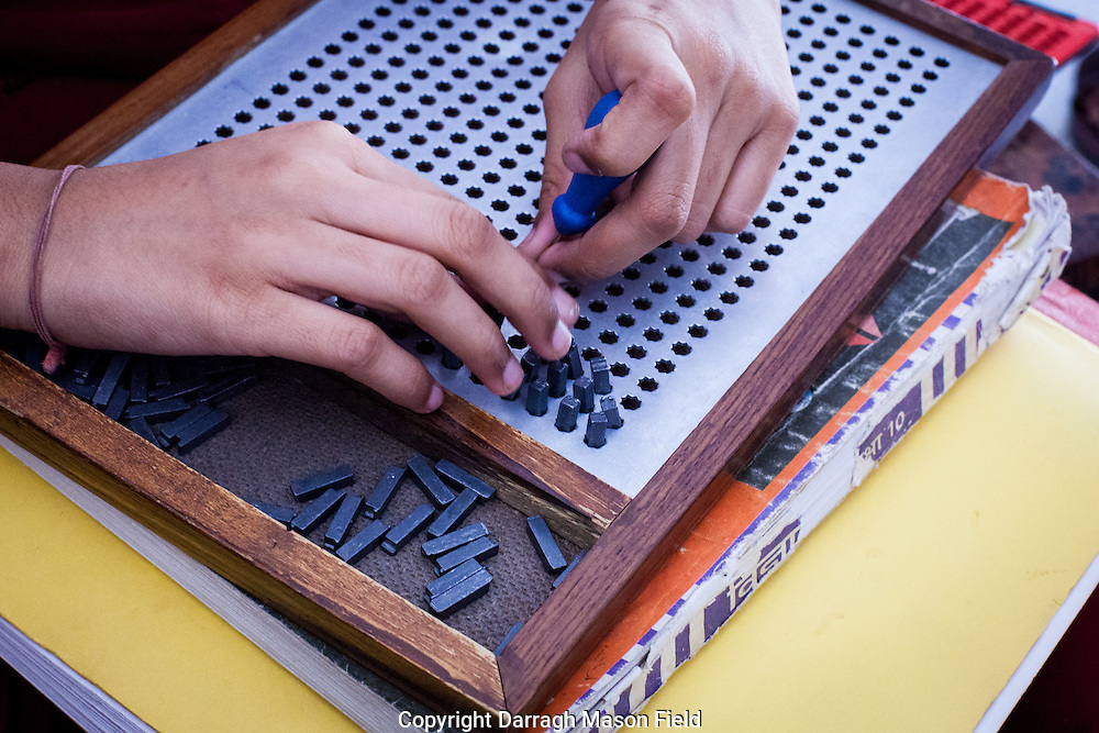 A female student uses a device for making calculations.  The metal studs represent numbers and rotating them changes there values.