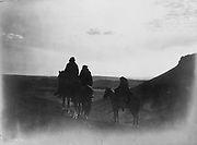Three Navaho Indians on horseback, silhouetted on black buttes (small hills) in evening light,1905.  Photograph by Edward Curtis (1868-1952).
