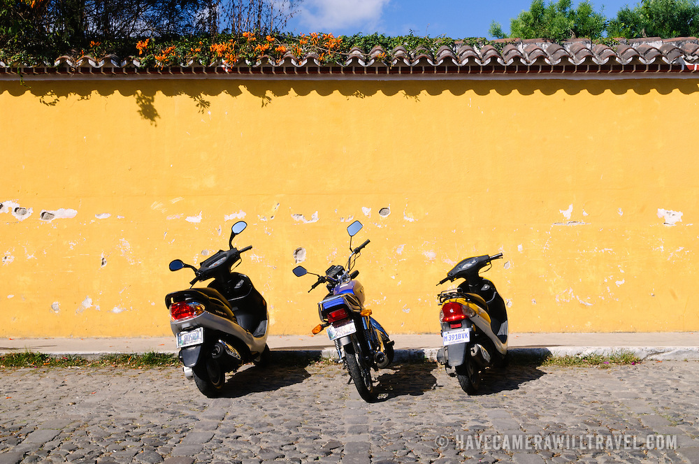 Three scooters parked on a cobblestone street in Antigua, Guatemala.