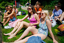 © Licensed to London News Pictures. 25/05/2017. London, UK. Emily Ashbrook and Elizabeth Bailey sunbathe in Hampstead Heath Mixed Bathing Pond in north London as temperatures hit 29C on Thursday 25 May 2017. Photo credit: Tolga Akmen/LNP