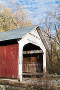 """Roseville Covered Bridge (263 feet long) was built in Burr Arch style over Big Raccoon Creek in 1910 by Van Fossen in Parke County, Indiana, USA. Red and white paint protects the wood. The traditional """"Cross this bridge at a walk"""" sign requires slow vehicle speed."""