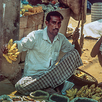 A street vendor hawks his fruits and lentils at his sidewalk display in Dhaka Bangladesh, 1977.