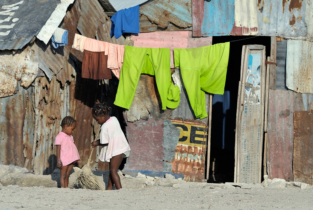 As her sister looks on, a girl sweeps the ground in front of her meager home in Cite Soleil, a sprawling poor portion of Port-au-Prince, Haiti.