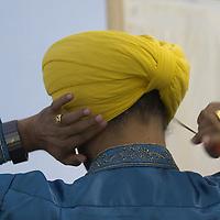 Singer adjusting his yellow turban,  Edinburgh MELA 2006<br />