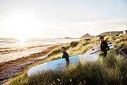 Father and son walking through the grassy sand dunes down onto the beach at St Ouen's Bay,  Jersey, ready for a surf.