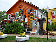"The Heidelberg Project: Bringing Colour, Art, and Controversy to a Decaying Part of Detroit<br /> <br /> Watching the deterioration of his impoverished, crime-ridden neighborhood of McDougall-Hall two decades after Detroit's 1967 race riots, artist Tyree Guyton felt the need to do something. So he picked up a paintbrush and painted pastel polka dots all over his grandfather's Heidelberg Street house.<br /> Guyton's paint job was the first act toward what became the Heidelberg Project, an outdoor community art project aimed at breathing life back into his decaying district. Encouraged by his grandfather, and with the help of local kids, Guyton began decorating the abandoned homes beside the polka-dot house and installing art made from salvaged materials.<br /> The project now spans two blocks and is constantly evolving, anchored by the altered houses. One ramshackle two-story home is covered in stuffed animals. Another is painted with numbers of wildly varying sizes and colors. Strewn across the yards are sculptures incorporating decorated cars, shopping carts, doors, shoes, and household appliances.<br /> Though the infusion of color and creativity has attracted a stream of appreciative visitors to McDougall-Hall, the Heidelberg Project has some vocal critics. Chief among them is the city of Detroit, which demolished parts of the community in 1991 and 1999.<br /> Local detractors view the Heidelberg Project as an eyesore and health hazard, and resent the fact that it draws further attention to Detroit's urban blight. On November 12 of this year, the project's ""House of Soul,"" an abandoned house decorated with hundreds of records, burned to the ground in a suspected arson attack. This followed a suspicious fire in May, in which an art-enhanced building called the ""Obstruction of Justice House"" was destroyed.<br /> Undeterred, Guyton has responded to the destruction with relentless optimism and vowed to continue expanding his vibrant art community.<br /> <br /> •Visit Atlas Obscura for more on the Heidelberg Project.<br />"