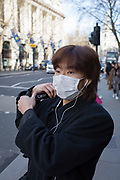 An Asian man wears a face mask on the street, on 16th february 2018, in London, England,