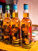 "11 MARCH 2016 - LUANG PRABANG, LAOS:  Fortified ""Lao Lao,"" a Lao rice whiskey, for sale in the handicraft market in Luang Prabang. It is fortified with dead cobras and scorpions. Luang Prabang was named a UNESCO World Heritage Site in 1995. The move saved the city's colonial architecture but the explosion of mass tourism has taken a toll on the city's soul. According to one recent study, a small plot of land that sold for $8,000 three years ago now goes for $120,000. Many longtime residents are selling their homes and moving to small developments around the city. The old homes are then converted to guesthouses, restaurants and spas. The city is famous for the morning ""tak bat,"" or monks' morning alms rounds. Every morning hundreds of Buddhist monks come out before dawn and walk in a silent procession through the city accepting alms from residents. Now, most of the people presenting alms to the monks are tourists, since so many Lao people have moved outside of the city center. About 50,000 people are thought to live in the Luang Prabang area, the city received more than 530,000 tourists in 2014.      PHOTO BY JACK KURTZ"
