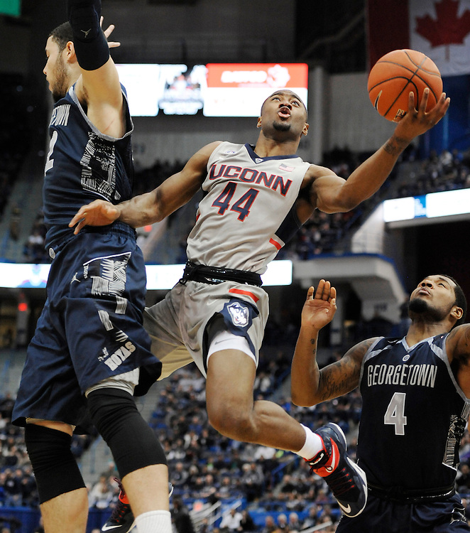 Connecticut's Rodney Purvis shoots between Georgetown's Bradley Hayes, left, and D'Vauntes Smith-Rivera, right, in the first half of an NCAA college basketball game, Saturday, Jan. 23, 2016, in Hartford, Conn. UConn won 68-62. (AP Photo/Jessica Hill)