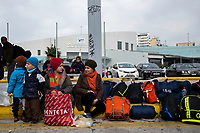 ATHENS, GREECE - FEBRUARY 04: Refugees sit on the ground outside the Pireaus port after disembarking a ferry from the Greek islands on February 04, 2015 in Athens, Greece. Thousands of refugees arrive every day by ferries fleet by private companies from the Greek islands to the Pireaus port, those with money can afford to buy tickets for the buses that will take them to the Macedonian border, but those arriving without money had to wait outside the Pireaus port for assistance or occupy spaces on public square in Athens where they will spend their days until the can travel Idomeni, near de Macedonian border. Photo: © Omar Havana. All Rights Are Reserved