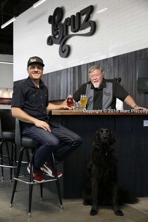 SHOT 7/22/16 1:43:49 PM - Bruz Beers co-founders Charlie Gottenkieny and Ryan Evans inside the new brewery near 67th Avenue and Pecos in Denver, Co. Bruz Beers is Denver's artisanal Belgian-style brewery, featuring a full line of traditional and Belgian-inspired brews, hand-crafted in small batches. Includes images of Evan's dog 'Cooper' as well who serves as the brewery dog. (Photo by Marc Piscotty / © 2016)