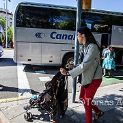 A tourist coach leaving its passengers in the middle of a pedestrian zone, blocking the way of a mother and her baby. Sagrada Família area.
