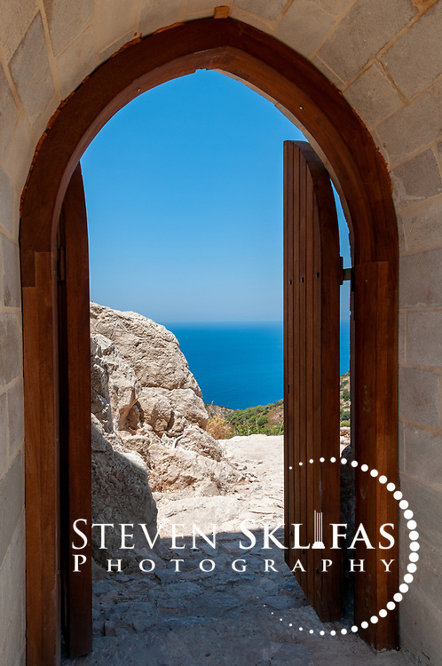 Rhodes. Greece. The blue Aegean Sea through the arched entrance to Kritinia Castle (Castle of Castello) on the west coast of Rhodes Island. Dating from 16th century the medieval strategic fortress was built by the Knights of St John and once boasted several coast of arms of several Grand Masters. It is surrounded by olive groves and pines wood and offers spectacular views of the Aegean Sea and the Wild West Coast of Rhodes Island. The island of Rhodes is the largest of the Dodecanese Island group and one of the most popular Greek Islands.