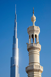 Contrasting view of Burj Khalifa tower and mosque minaret in Dubai United Arab Emirates