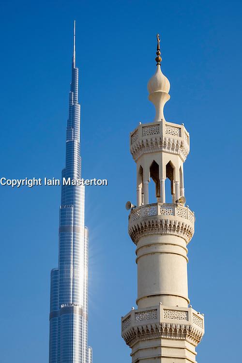 Contrasting view of Burj Khalifa tower and mosque minaret in Dubai United Arab Emirates