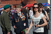 Moscow, Russia, 07/05/2010..Two young women walk past a war veteran near the Kremlin in the lead-up to the forthcoming May 9 Victory Day parade, scheduled to be the largest for many years.