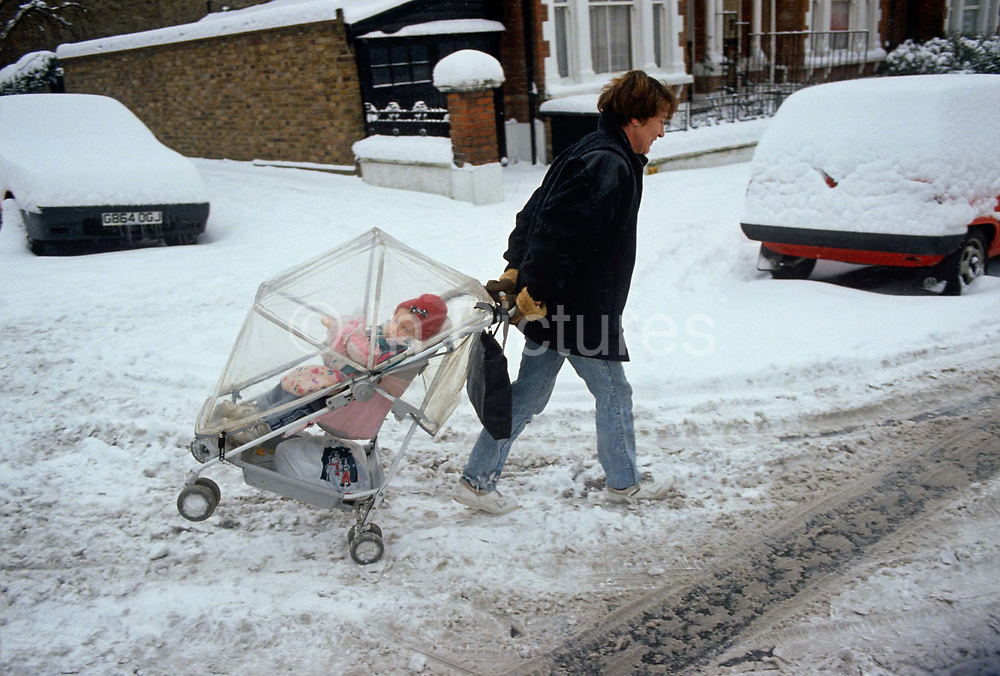 A mother struggles to pull her young child over freshly fallen snow in a London street. With the child's tilted pushchair skating over compacted snow driven over many car tyres, the lady wears trainers that are themselves, ill-suited to walking though snow. Nearby vehicles are still covered in snow, having been left during this urban cold snap, something that Londoners are learning to cope with during times of economic council cuts when snow-clearing is not a spending priority.