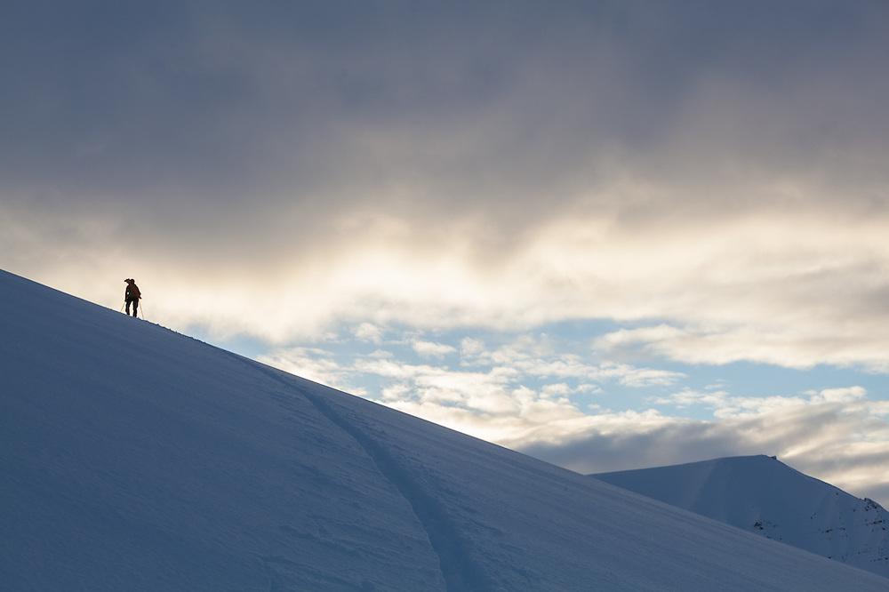 Mylène Jacquemart silhouetted at sunset on Hallwylfjellet, Svalbard.