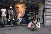 Eccentric woman shopper and a large image of a male model in the window of clothing retailer H&M on Regents Street, London borough of Westminster.