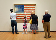 © Licensed to London News Pictures. 28/05/2012. New York, USA People listen to an audio tour whilst a young girl points at a painting of an American flag by artist Jasper Johns at the Museum of Modern Art (MoMA) in New York today 28 march 2012. Photo credit : Stephen Simpson/LNP