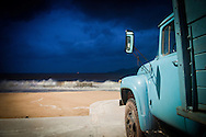 Old truck parked in front of the beach in Nha Trang, Vietnam, Asia. Very heavy and dramatic dark blue sky in background. Ray of sun hit the vehicle and the sand. Strong weave hit the shore.