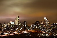 New York City and the Queensboro bridge at night on a Fall evening as the city lights light up the stormy clouds overhead.