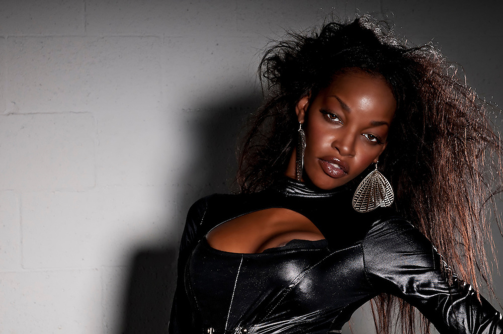Sensual African American with leather catsuit posing.