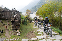 Round the World Doug Wothke riding up a stone path into another village on Motorcycle Sherpa's Ride to the Heavens motorcycle adventure in the Himalayas of Nepal. On the fourth day of riding, we went from Kalopani to Muktinath. Thursday, November 7, 2019. Photography ©2019 Michael Lichter.