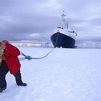 Antarctic Peninsula, Antarctica. A polar tourist pretends to pull a cruise ship.