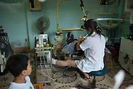 Hanoi, Vietnam - July 25, 2008 -- A dentist, her foot in a cast, works on a man in Hanoi. Photo taken through a window from the sidewalk.
