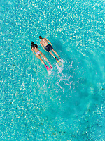 Aerial view of man and woman snorkeling next to each other in masks and flippers in turquoise sea.