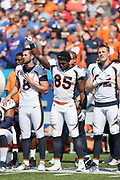 Denver Broncos kicker Brandon McManus (8) and Denver Broncos tight end Jeff Heuerman (82) stand with their hands over their hearts while Denver Broncos tight end Virgil Green (85) holds his fist in the air during the playing of the National Anthem before the 2017 NFL week 3 regular season football game against the against the Buffalo Bills, Sunday, Sept. 24, 2017 in Orchard Park, N.Y. The Bills won the game 26-16. (©Paul Anthony Spinelli)