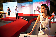 Shoppers watch a massive PR promotional push by cell phone company Mororola. Following a stage presentation with models and large screens, the mobile phone giant has staff selling phones to customers as well as fun and giving away gifts by way of mass marketing. Crowds gathered to watch and buy. Xidan is one of the main commercial shopping area in the Xicheng district of Beijing, China. With Joy City as it's centerpiece, a 13-story coplex of western and Chinese shops. This is a shoppers haven as modern consumerism and commerce have a strong grip on Beijing's shop hungry crowds.