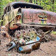 An old car, next to two different engine blocks, is slowly rusting away at the Old Car City junkyard in Georgia.